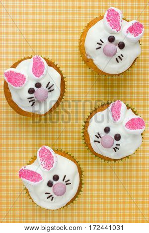 Easter bunny face cupcakes on yellow background top view