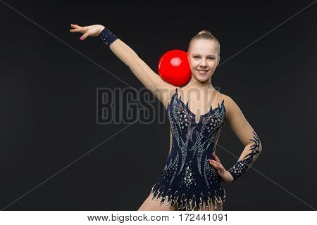 Beautiful blond gymnastist girl in black sparkling cistume holding red ball over black background