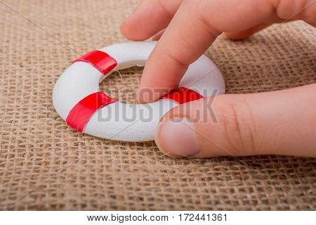 Hand Holding A Lifesaver On Fabric
