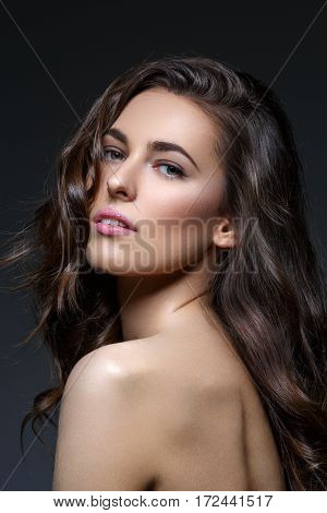 Beautiful brunette young woman with long healthy thick wavy hair and make-up on black background. Copy space.