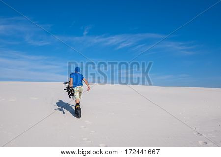 Sporty Man With A Snowboard Goes Up The Sand Dune