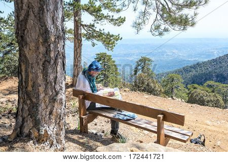Bearded Man Is Sitting On A Bench With A Map