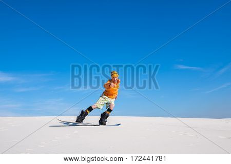 Man Rides On The Snowboard In Desert