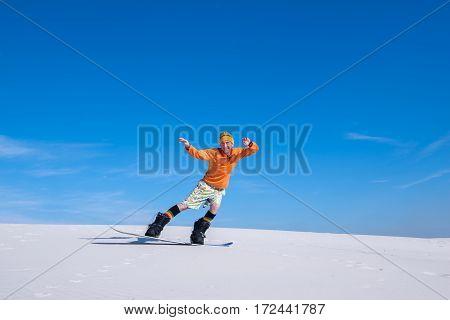 Joyful Man Rides On The Snowboard In Desert