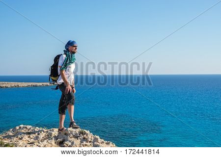 Bearded Man Hipster With Backpack Stands On A Rocky Seashore