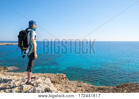 Traveler Bearded Man With Backpack Stands On A Rocky Seashore