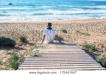 Man traveler sits on the edge of a wooden pier near the sea and admiring the surf. Sunny day on the peninsula Akamas Cyprus. Back view.