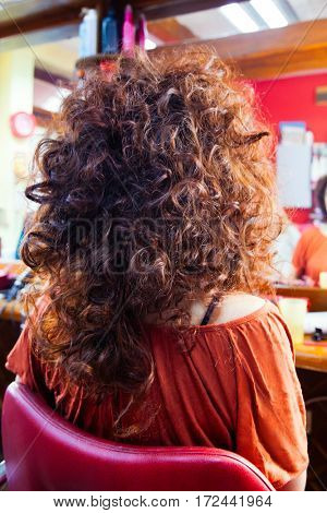 woman with long curly hair at hairdresser back view closeup
