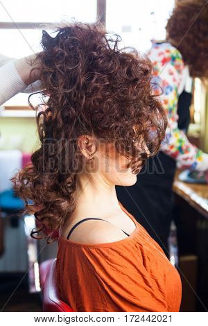 woman with raised  long curly hair in elegant style at hairdresser closeup