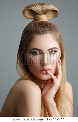 Beautiful young woman with long straight blond hair and fancy hairdo on top of head. Eyes closed. Studio shot on grey background. Copy space.