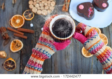 cup of black coffee in his hands over the table his hands on a colorful knitting mittens