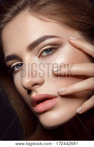 Close-up portrait of beautiful young woman with natural beige tone make up and manicure