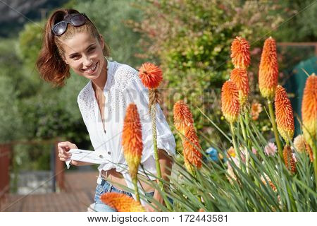 Young beautiful girl enjoying on the  flowers field, outdoor portrait, summer fun concept, beautiful woman relaxing in the floral garden, female at fresh spring meadow.