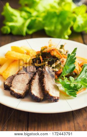 Roast Beef Sliced Slices With Fries And Greens. Wooden Background. Close-up