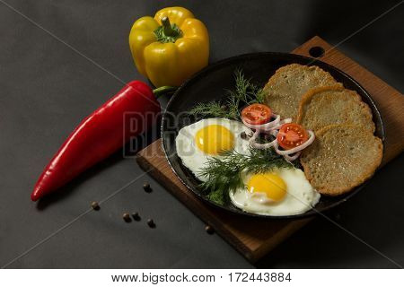 Fried Eggs With Potato Pancakes And Herbs In A Pan On A Black Background. Homemade Food.
