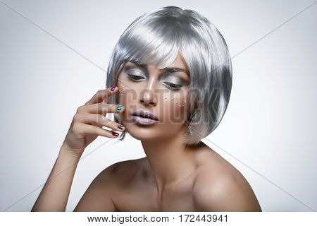 Beautiful young woman with glowing skin, fashion make-up and metallic nails in short silver hair wig. Beauty shot on white background. Copy space.