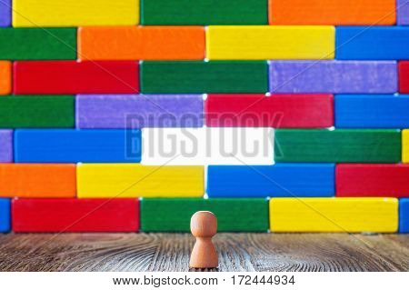 Abstract man standing in front of a wall or barrier of multicolored wooden blocks through which the light shines. Success concept. Business metaphor.