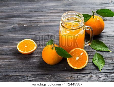 Freshly squeezed orange juice in a mason jar and fresh oranges fruits with green wet leaves on a wooden rustic table with copy space.