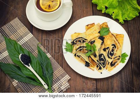 Rolls Pancakes With Black Caviar. Russian Cuisine. Flat Lay. Maslenitsa. Wooden Background. Top View