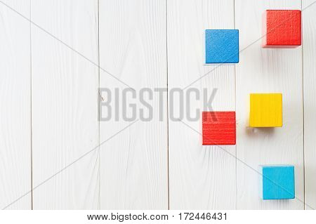 Wooden cubes on a white background top view. Concept of creative logical thinking. Colorful shapes wooden blocks on white wooden background flat lay copy space. Abstract Background.