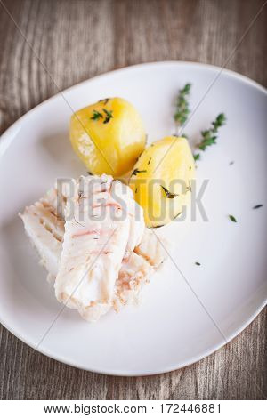 Steamed fish and potato on a white plate