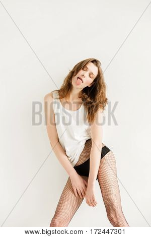 Young woman with brown hair in a white shirt and black stockings and shoes on a white background. The woman has fun. Woman shows tongue Woman without makeup. Model test. Fashion model. Facial. Type a strong face. Emotional girl. Emotions on face