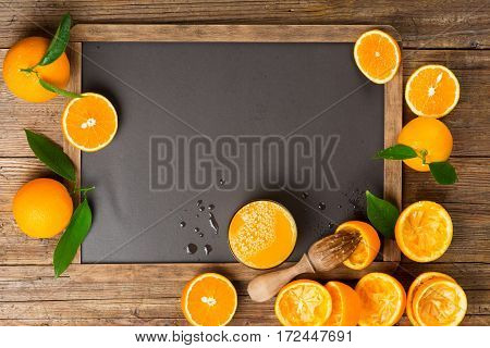 Orange juice with squeezed orange fruits on a blank blackboard with copy space.