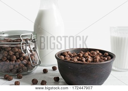 chocolate cornflakes bowl in a bowl with milk on white wooden background. breakfast