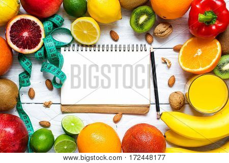 fresh fruits and vegetables with nuts for healthy diet on white wooden table. fitness concept with notebook and type measure. top view