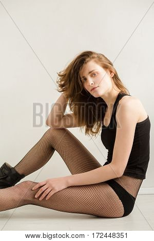Young woman with brown hair in a black shirt and black tights and boots sitting on the floor on a white background. A woman without makeup. Model test. Fashion model. Type a strong face.