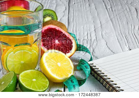 Fitness concept with fruits and detox water. Fitness motivation with centimeter and notebook on white wooden background. close up