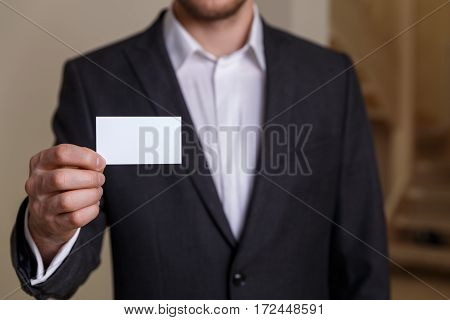 Businessman holding visit card. Man showing blank business card. Person in black suit. Mock up design.