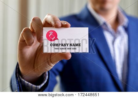 Businessman holding visit card. Man showing blank business card with company name text. Person in blue suit. Mock up design.