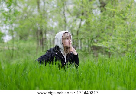 a girl on a forest glade sitting in a grass