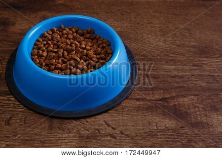 Bowl of dry kibble dog food. Healthy pets feed. Blue plate on wooden rustic background. poster