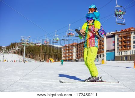 Father carrying tired son in skiing outfit on shoulders. Standing on ski with chairlifts.