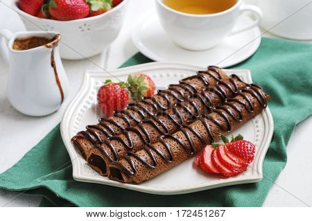 Chocolate crepes with cup of tea and fresh strawberries