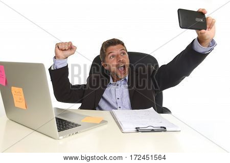 young attractive and happy businessman in suit working at office laptop computer desk using mobile phone for taking selfie photo raising arm in victory sign isolated on white background
