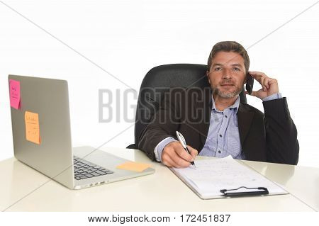 young attractive businessman in suit working at laptop computer desk talking on mobile phone at modern office writing notes with pen on notepad isolated on white background