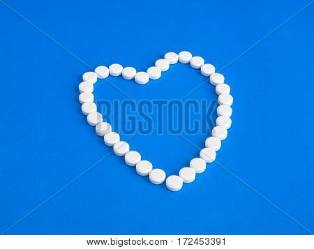 White pills on a blue background. Heart.