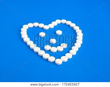 White pills on a blue background. Heart and smile/