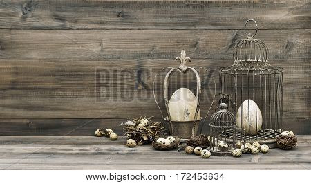 Easter decoration with eggs nest and birdcage. Vintage style toned picture