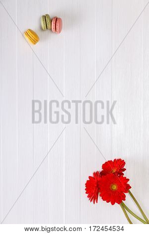 Macaroon cakes with red Gerbera flowers. Different types of macaron. Colorful almond cookies. On white wooden rustic background.