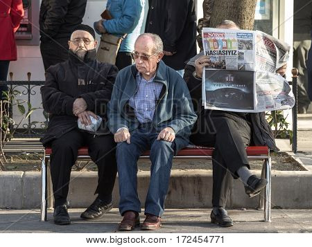 ISTANBUL TURKEY - DECEMBER 28 2015: Three old Turkish men sitting on a bench near Kadikoy district on the Asian side of the city one of them reading Sozcu Newspaper