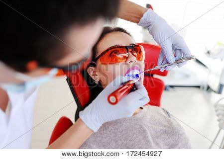 dentist makes dental fillings pretty young girl patient. Ultraviolet lamp for tooth enamel in the mouth