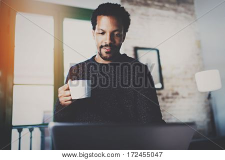 Cheerful African man using computer and smiling at the living room.Black guy holding ceramic cup in hand.Concept of young business people working at home.Blurred background.Selective focus
