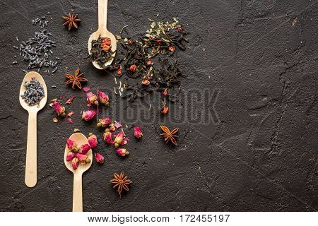 Herbs on spoons black stone background mock-up top view