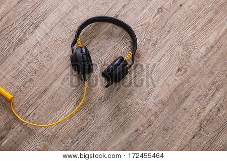 Headphones with yellow cable. Modern device for listening music. Sound earphones lying on wooden rustic background.
