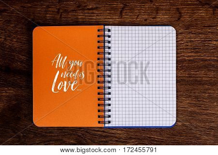 Notepad with All you need is love text. Mockup design concept with empty notebook page. Mock-up of blank diary. Wooden rustic desk.