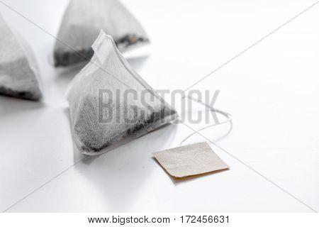 Three triangle teabags of black tea on white table background mockup